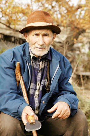Senior man in casual sitting outdoors while holding trowel photo