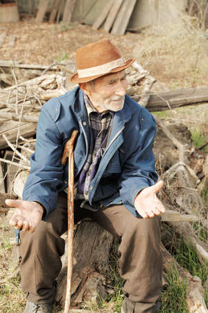 grayness: Senior man gesticulating while sitting outdoors Stock Photo