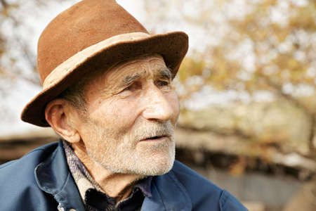 Senior man in hat looking sideways outdoor portrait photo