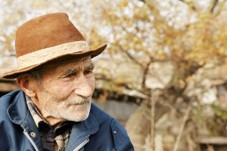 Sad senior man in hat looking sideways outdoor portrait Stock Photo
