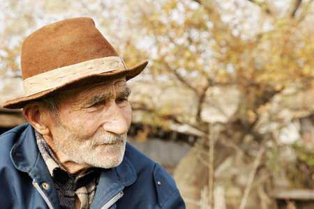 grayness: Triste uomo anziano in cappello cercando lateralmente ritratto all'aperto