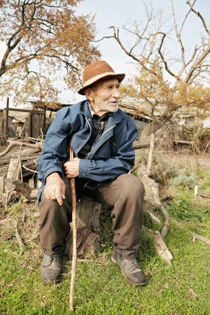 Senior man with stick sitting on stump outdoors photo