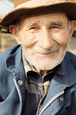 grayness: Outdoor portrait of smiling senior man in hat Stock Photo