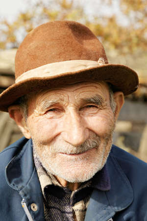 old man smiling: Outdoor portrait of positive senior man in hat Stock Photo