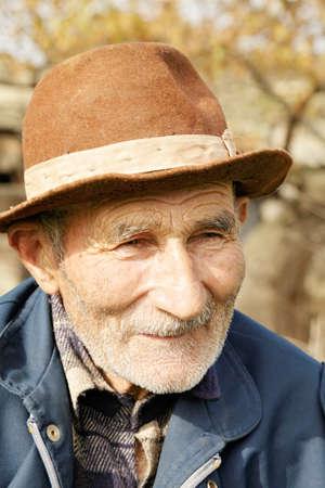 Senior man in hat looking sideways photo