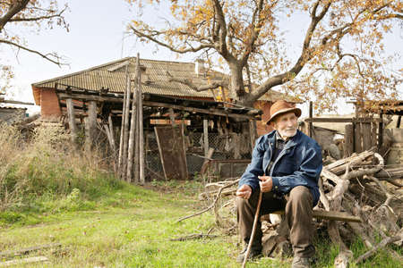 Senior man with stick sitting outdoors on firewood heap against old house photo