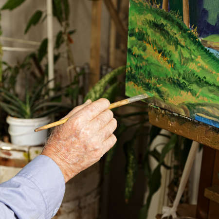 Artist's hand with paintbrush at painting process Stock Photo - 15862870