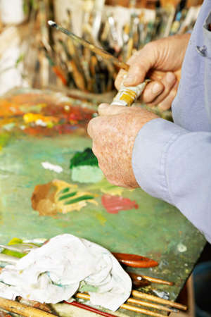 Painter hands with paint tube over palette Stock Photo - 15862895