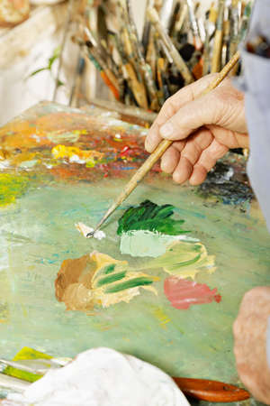 Painter hands mixing paints on palette Stock Photo - 15862893