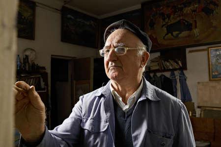 artistas: Artista en el caballete de taller en contra de las im�genes colgadas en las paredes Foto de archivo