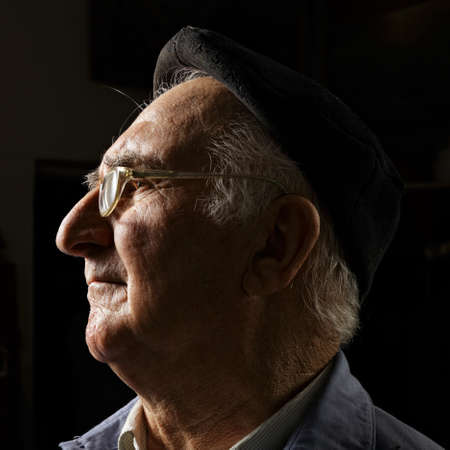 Senior in cap and eyeglasses sideview head and shoulders portrait photo