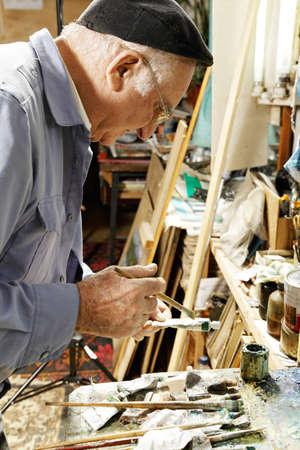 Painter holding paint tube and paintbrush