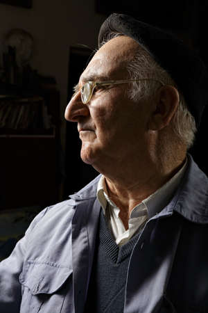 Elderly man in cap and eyeglasses sideview in darkness photo