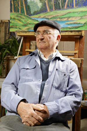 Artist sitting in chair under his painting looking sideways photo