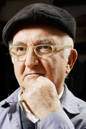 Elderly pensive man in cap and eyeglasses leaning on hand photo