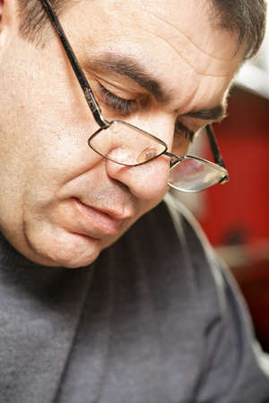 Portrait of middle-aged caucasian man in eyeglasses looking down photo