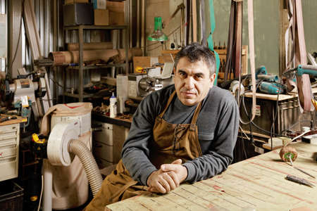 sitting small: Middle-aged craftsman sitting in his workshop at workbench