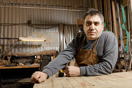 Caucasian middle-aged artisan sitting in his workshop at workbench low angle view