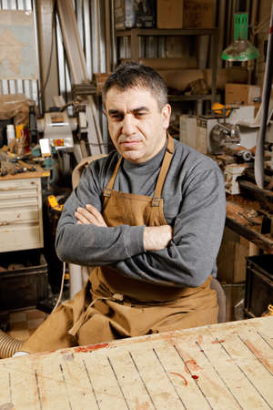 looking sideways: Artisan looking sideways sitting at workbench arms folded