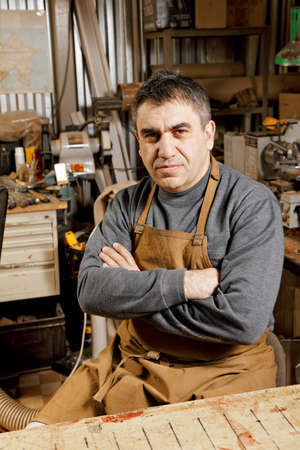 Artisan looking to camera sitting at workbench arms folded