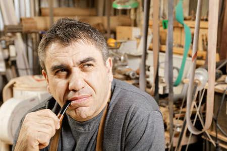 looking sideways: Serious caucasian guy smoking pipe in workshop and looking sideways Stock Photo