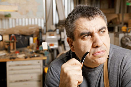 Middle-aged man with smoking pipe sitting in his workshop and looking sideways photo