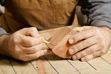 billet: Artisan hands sketching on wood billet at workbench