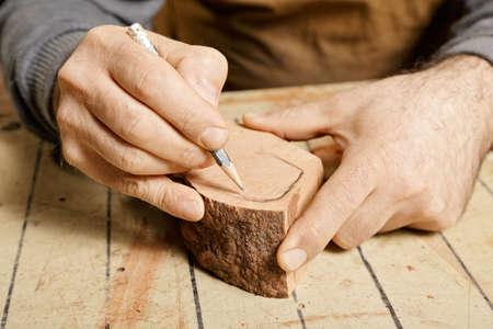 billet: Woodworker hands sketching on wood billet at workbench Stock Photo