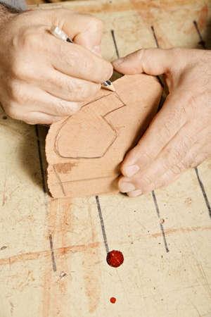 billet: Artisan hands sketching pipe on wood billet