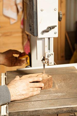 billet: Artisan hands sawing billet at bandsaw while making pipe