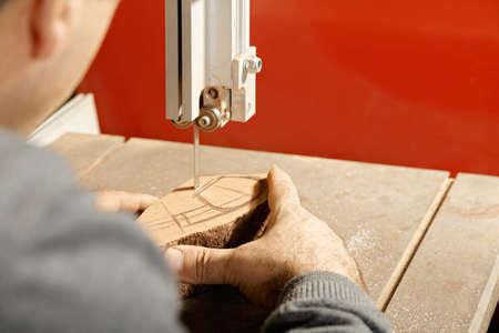 billet: Artisan sawing billet at bandsaw while making smoking pipe rear view