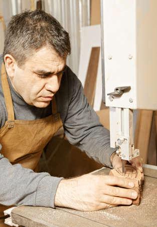 billet: Craftsman sawing billet at bandsaw while making smoking pipe Stock Photo