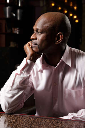 Sideview portrait of african man in pink shirt sitting at desk ornated with coffee beans photo