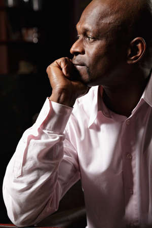 Sideview portrait of pensive african man in pink shirt Stock Photo - 16142263