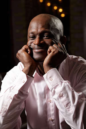Portrait of contented african man in pink shirt leaning on fists Stock Photo - 16142265