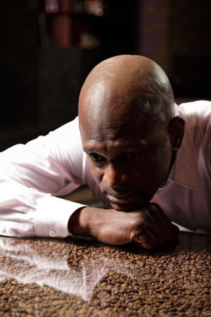 Portrait of sad african man in pink shirt leaning on desk ornated with coffee beans Stock Photo - 16142260