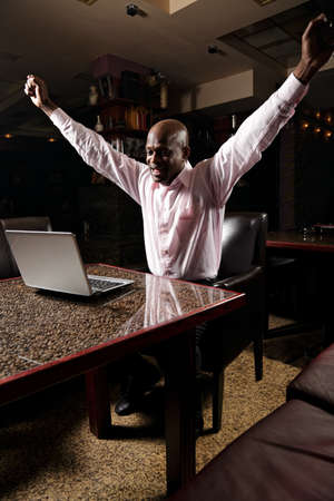 Happy african businessman jumping out of cafe table while looking at laptop monitor photo