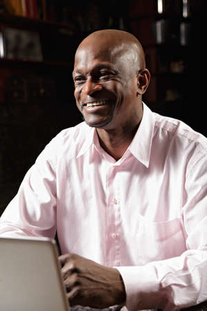 Smiling african man in pink shirt working at laptop and looking sideways Stock Photo - 16142269