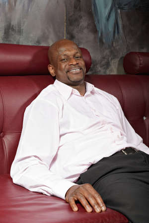 Relaxed middle aged african man sitting on red leather sofa Stock Photo - 16142262