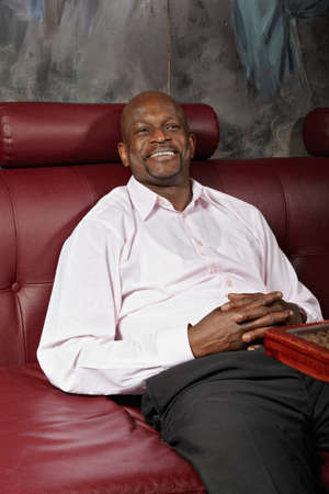 Positive middle-aged african man sitting on red leather sofa photo