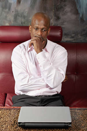 Pensive african guy in pink shirt sitting on sofa at table with closed laptop photo
