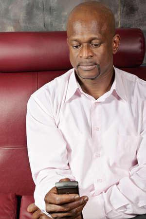 African man in pink shirt texting on mobile while sitting on red sofa photo