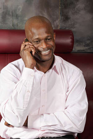 Positive african man in pink shirt talking on mobile phone photo