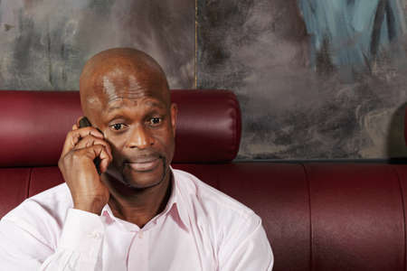 Surprized african man in pink shirt talking on mobile phone Stock Photo - 16142271