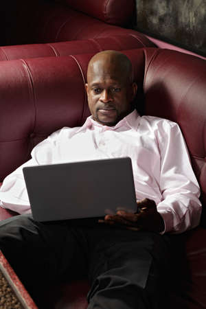 African guy in pink shirt with laptop laying down on sofa photo