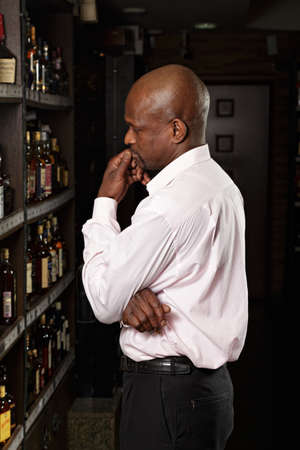African guy in a wine shop examining shelves photo
