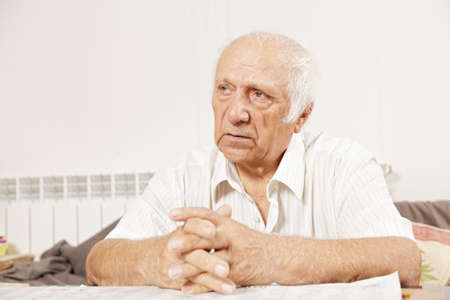 Senior serious man in white shirt sitting at table and looking sideways Stock Photo