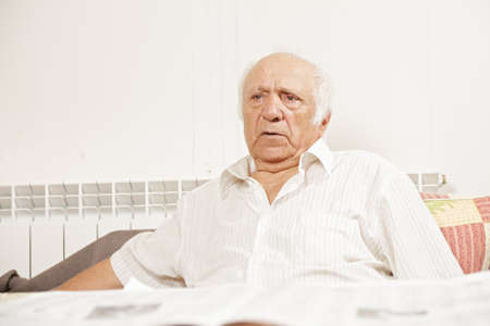Senior man in white shirt with newspaper sitting on sofa