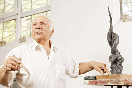 Senior sculptor describing his sculpture in workshop low angle view Stock Photo - 16469190