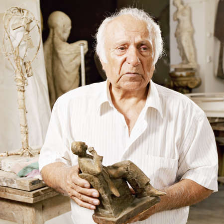 Senior sculptor holding his sculpture and looking sideways Stock Photo - 16469192